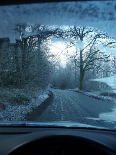 inside a car dirving along a frosty winter english lane